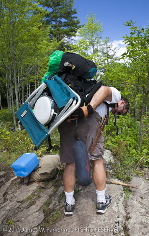Overloaded backpacker with loads both front and back