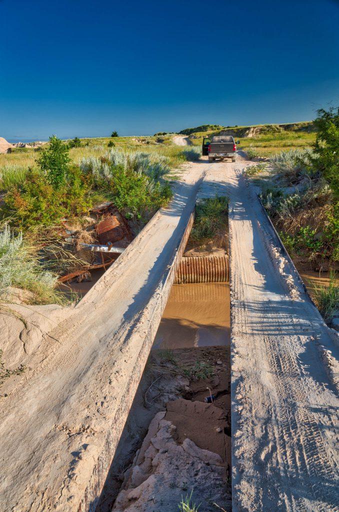 two steel beams bridge the creek