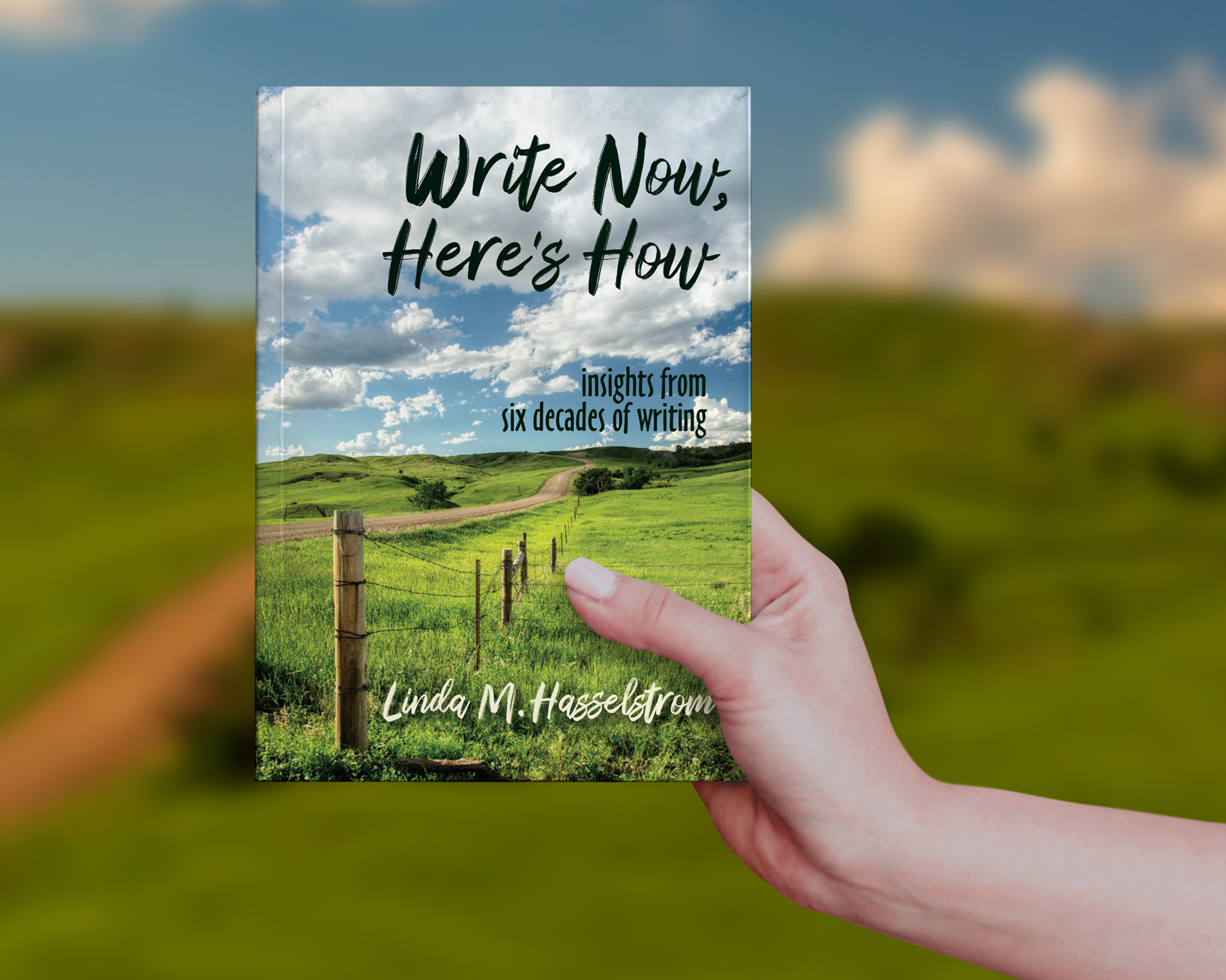 woman holding paperback book with prairie background